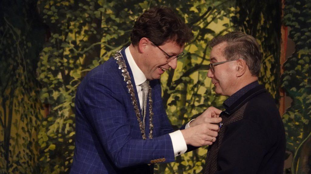 Jan Schenkel krijgt de onderscheiding opgespeld door de burgemeester