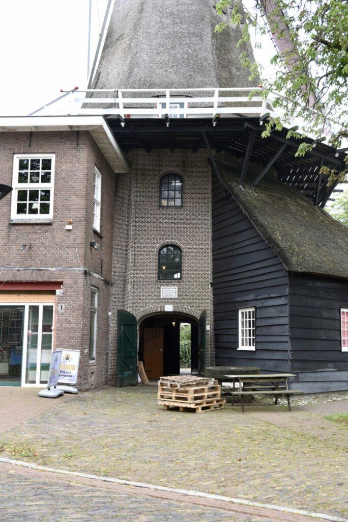 entree, links de stenen, rechts de rietgedekte houten uitbouw